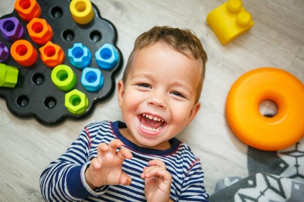 Glücklicher kleiner junge, der den spaß lacht auf der boden- draufsicht hat