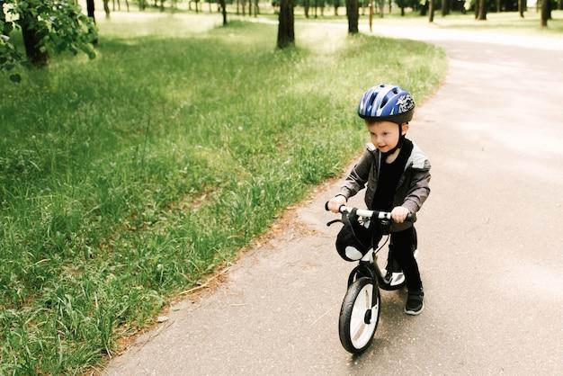 Glücklicher kleiner junge, der ein fahrrad fährt, das im park läuft