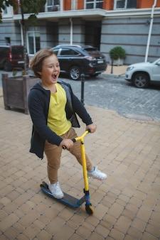 Glücklicher kleiner junge, der einen roller auf stadtstraßen reitend genießt