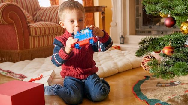 Glücklicher kleiner junge, der einen spielzeugzug anschaut und anlächelt, den er zu weihnachten bekam. kind bekommt geschenke zu neujahr