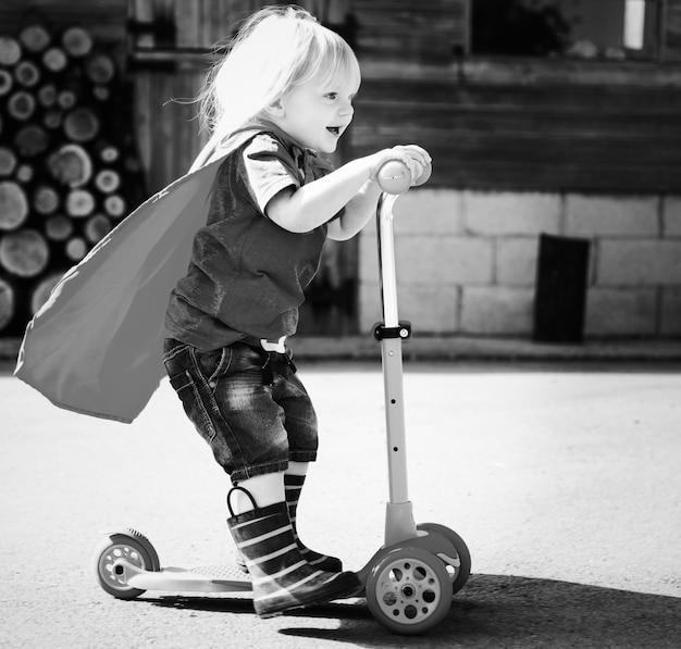 Glücklicher kleiner junge, der eingebildeten superhelden spielt