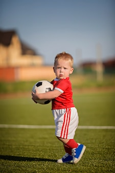Glücklicher kleiner junge, der fußball mit ball auf feld nahe tor spielt