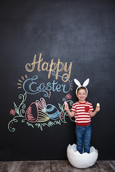 Glücklicher kleiner junge, der hasenohren trägt und in der großen rissigen eierschale steht