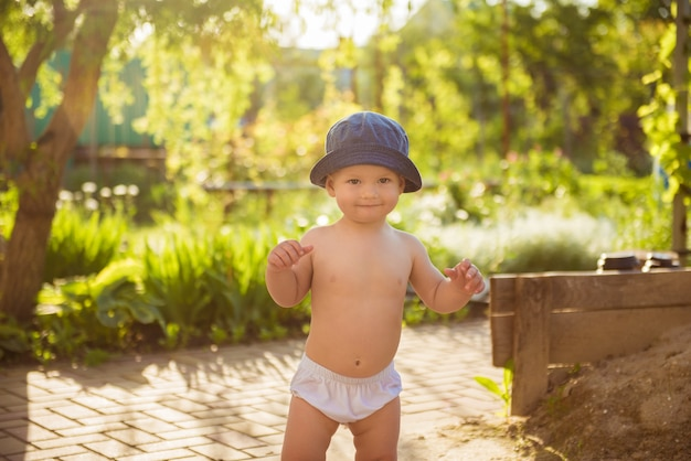 Glücklicher kleiner junge, der im park in einem lustigen panamahut spielt