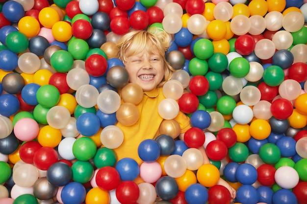 Glücklicher kleiner junge, der im pool mit farbigen kugeln liegt und das spiel genießt