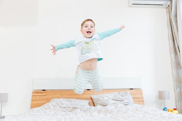 Glücklicher kleiner junge, der im schlafzimmer auf bett springt