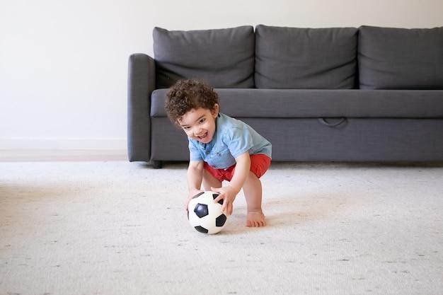 Glücklicher kleiner junge, der mit fußball zu hause spielt und lächelt. nettes kind, das barfuß auf teppich steht und spaß im wohnzimmer hat. ferien-, wochenend- und kindheitskonzept