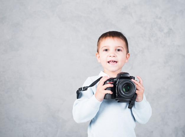 Glücklicher kleiner junge, der mit kamera steht
