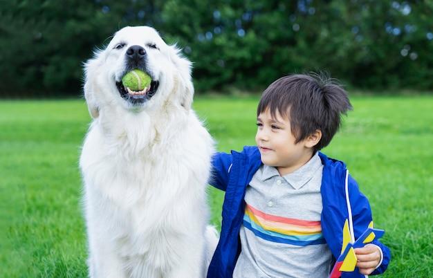 Glücklicher kleiner junge, der mit seinem hund im park spielt