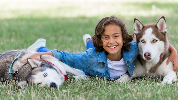 Glücklicher kleiner junge, der mit seinen hunden am park spielt