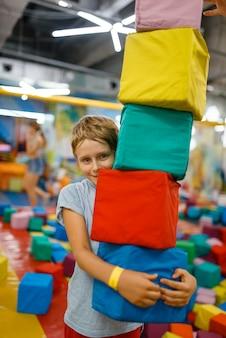 Glücklicher kleiner junge, der mit weichen würfeln, spielplatz im unterhaltungszentrum spielt. spielbereich drinnen, spielzimmer