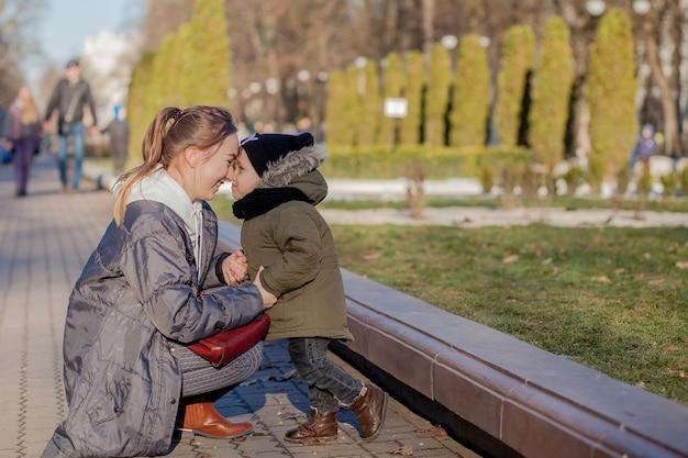 Glücklicher kleiner junge, der mutter draußen küsst. muttertag