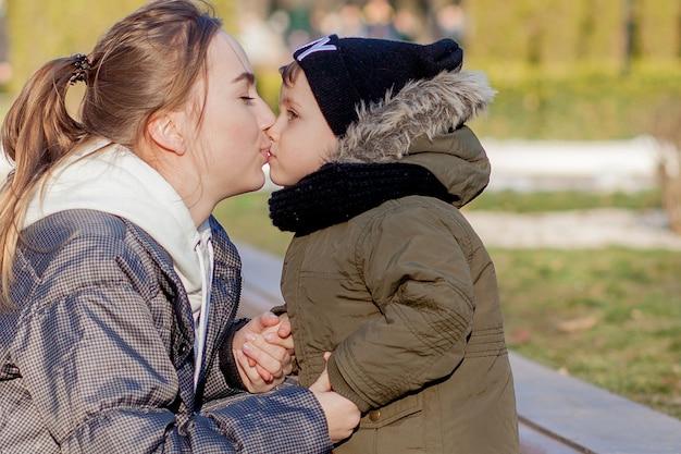 Glücklicher kleiner junge, der mutter draußen küsst.