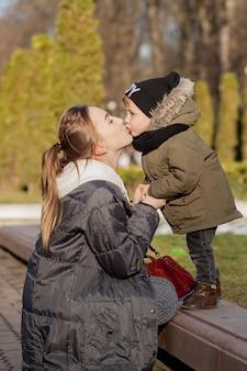Glücklicher kleiner junge, der mutter draußen küsst