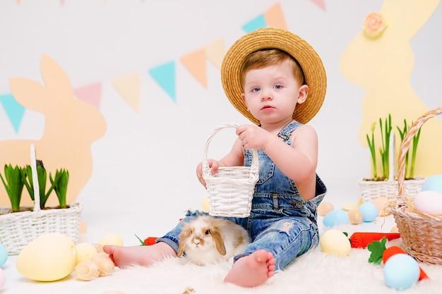 Glücklicher kleiner junge, der niedlichen flauschigen hasen nahe gemalten ostereiern hält