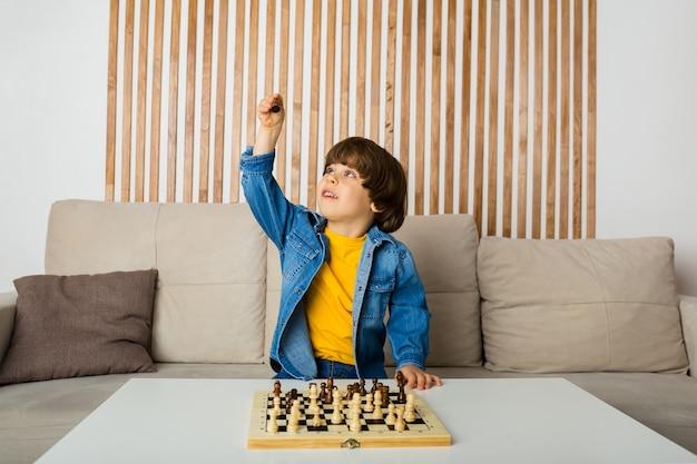 Glücklicher kleiner junge, der schach am tisch im raum spielt