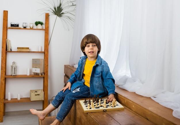 Glücklicher kleiner junge, der schach im raum spielt