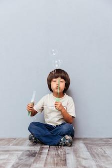 Glücklicher kleiner junge, der seifenblasen sitzt und bläst