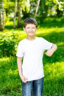Glücklicher kleiner junge, der seine finger auf einem leeren t-shirt zeigt.