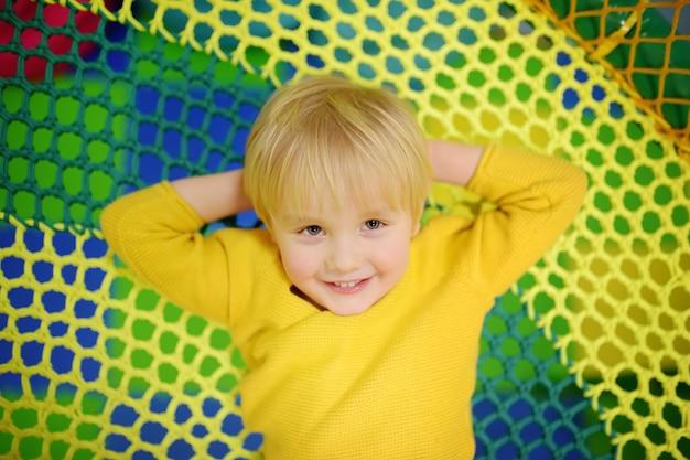 Glücklicher kleiner junge, der spaß in der unterhaltung in der spielmitte hat