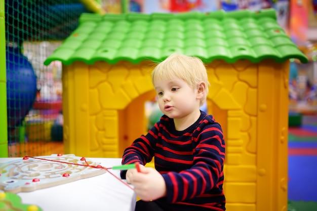 Glücklicher kleiner junge, der spaß mit pädagogischem spielzeug in der spielmitte hat
