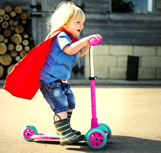 Glücklicher kleiner junge, der superheld spielt
