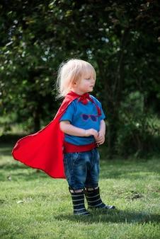Glücklicher kleiner junge, der superhelden mit fantasie spielt