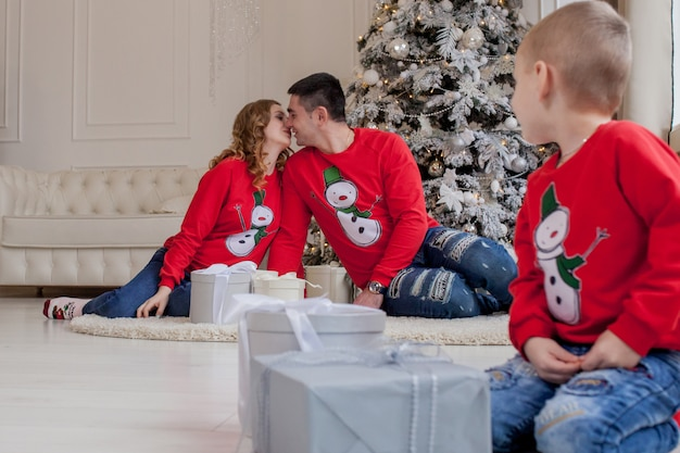Glücklicher kleiner junge, der weihnachtsgeschenke nahe neujahr öffnet