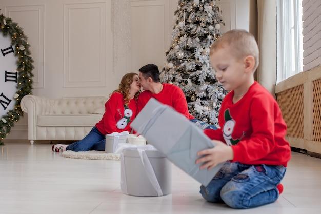 Glücklicher kleiner junge, der weihnachtsgeschenke öffnet