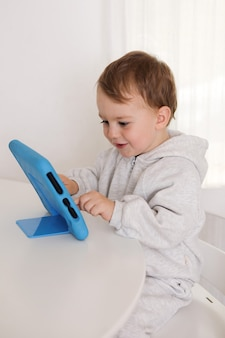 Glücklicher kleiner junge, der zu hause spiel auf digitalem tablett spielt. porträt eines kindes zu hause, das cartoon auf dem tablet ansieht. moderne kinder- und bildungstechnologie.