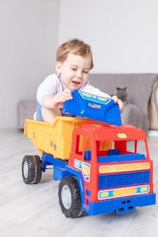 Glücklicher kleiner junge, der zu hause spielt und in einer schreibmaschine reitet, das konzept eines kinderspiels