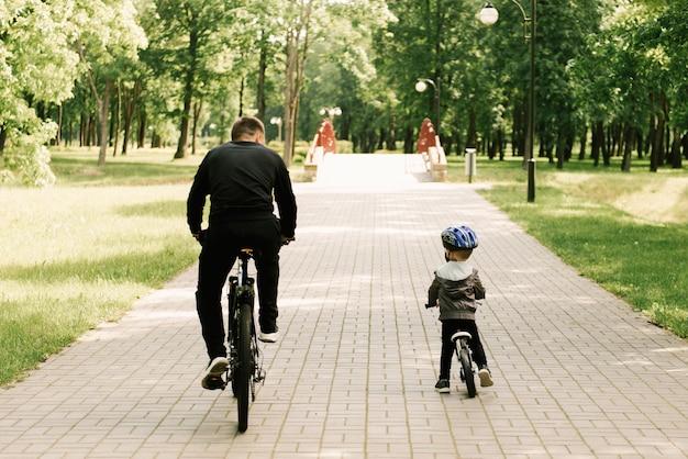Glücklicher kleiner junge fährt fahrrad mit einem jungen vater im park