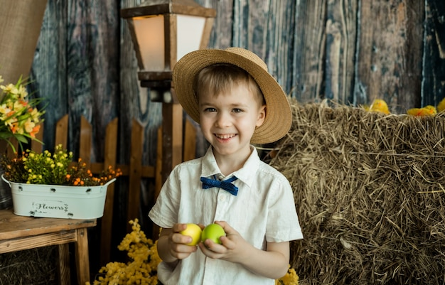 Glücklicher kleiner junge gentleman steht mit bunten eiern in rustikalen osterdekorationen