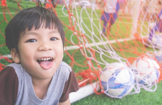 Glücklicher kleiner junge hinter dem ziel im fußballtrainingsfeld