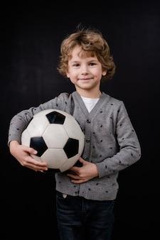 Glücklicher kleiner junge in der freizeitkleidung, die fußball durch brust isoliert hält