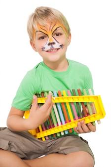 Glücklicher kleiner junge in der tigergesichtsfarbe, die xylophon spielt