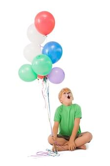 Glücklicher kleiner junge in der tigergesichtsfarbe mit ballonen