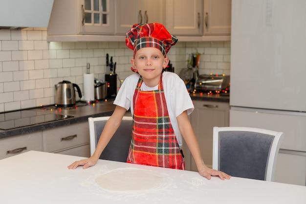 Glücklicher kleiner junge kocht weihnachtsplätzchen zu hause in der küche in einem kochkostüm