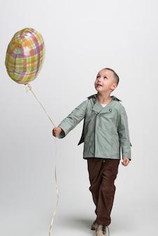 Glücklicher kleiner junge mit ballon auf weißem hintergrund, studioaufnahme