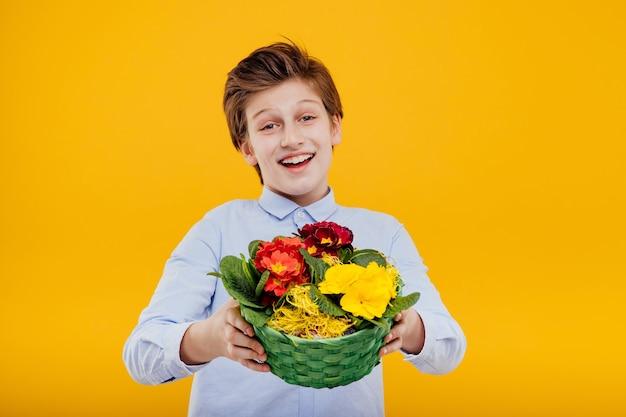Glücklicher kleiner junge mit blumenkorb in seiner hand, im blauen hemd, lokalisiert auf gelber wand