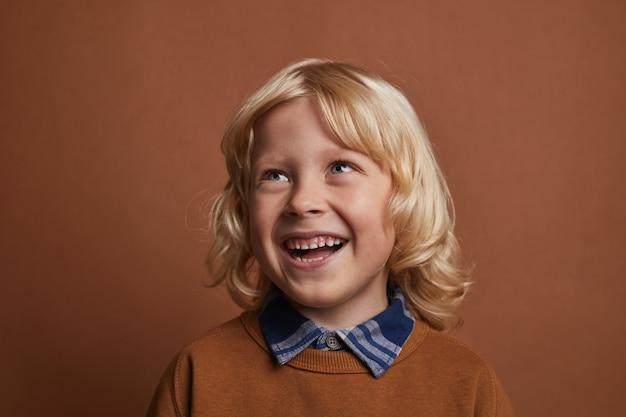 Glücklicher kleiner junge mit dem blonden haar, das hemd und pullover trägt, die gegen den braunen hintergrund stehen