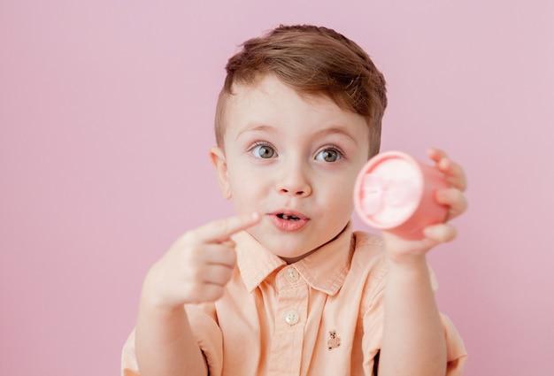 Glücklicher kleiner junge mit einem geschenk. foto lokalisiert auf rosa hintergrund. lächelnder junge hält geschenkbox