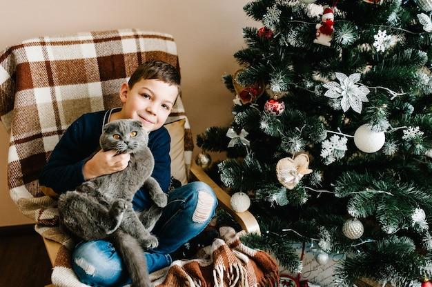 Glücklicher kleiner junge mit katze - weihnachtsgeschenk, das nahe weihnachtsbaum zu hause sitzt. nettes kind drinnen.