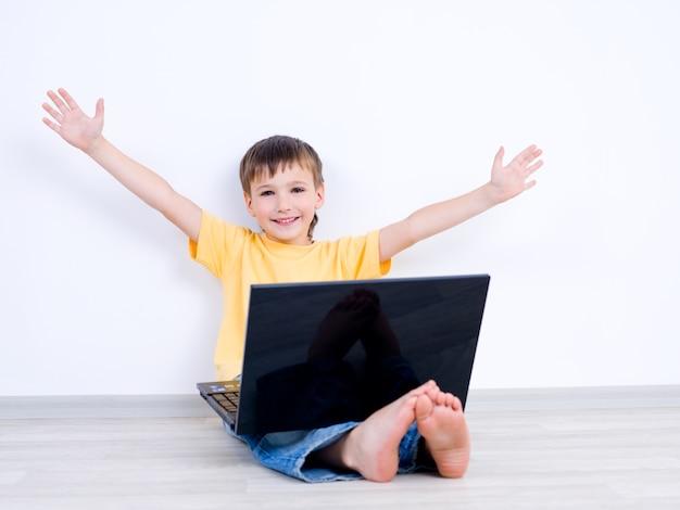 Glücklicher kleiner junge mit laptop mit auseinander bewegenden händen - drinnen