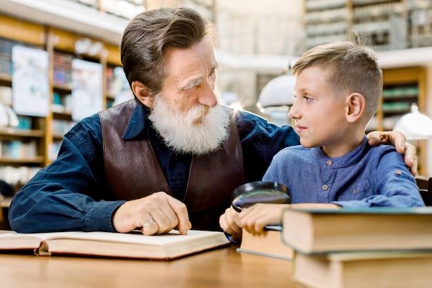 Glücklicher kleiner junge mit seinem fröhlichen bärtigen großvater, der bücher in der bibliothek liest und einander schaut. lächelnder kleiner junge mit seinem älteren lehrer, der zusammen in der vintage-bibliothek studiert