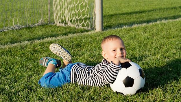 Glücklicher kleiner junge mit seinem fußball, der auf dem üppigen grünen gras eines sommersportplatzes im abendsonnenlicht liegt