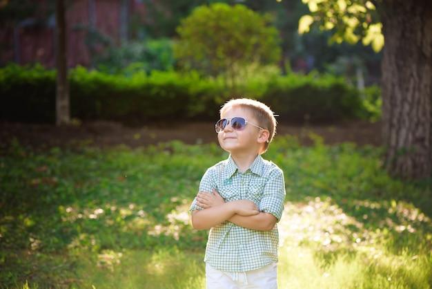 Glücklicher kleiner junge mit sonnenbrille im garten.