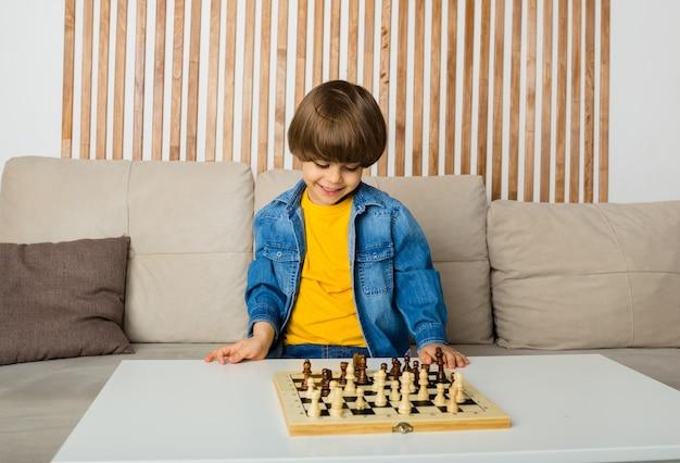 Glücklicher kleiner junge sitzt in einem raum, der schach spielt