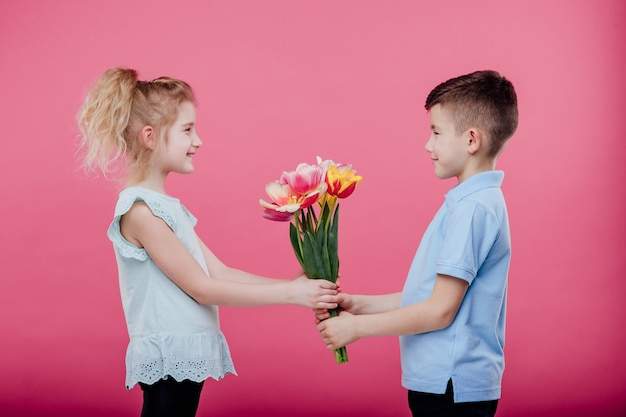 Glücklicher kleiner junge streckt blumen zu einem kleinen mädchen im rosa kleid, lokalisiert auf blauer wand, seitenansicht