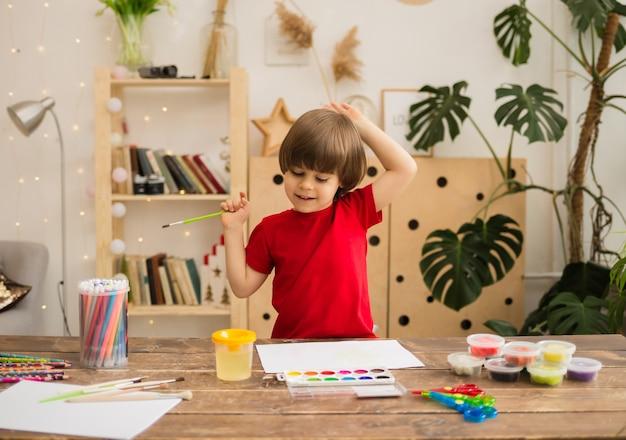Glücklicher kleiner junge zeichnet mit einem pinsel und malt auf weißem papier auf einem holzschreibtisch mit briefpapier